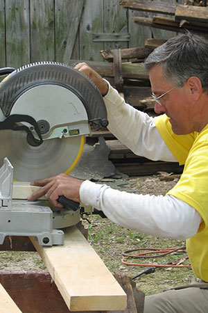 Volunteer using a miter saw